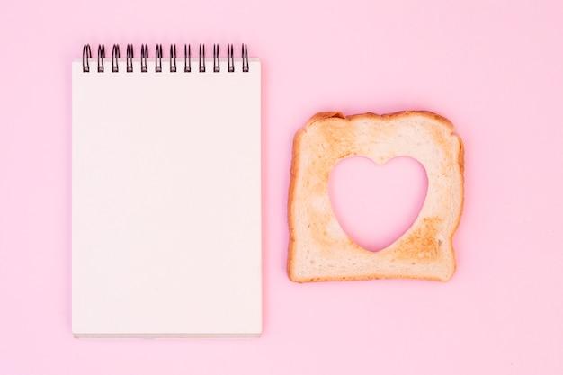 Rebanada de pan con el corazón cortado y la libreta