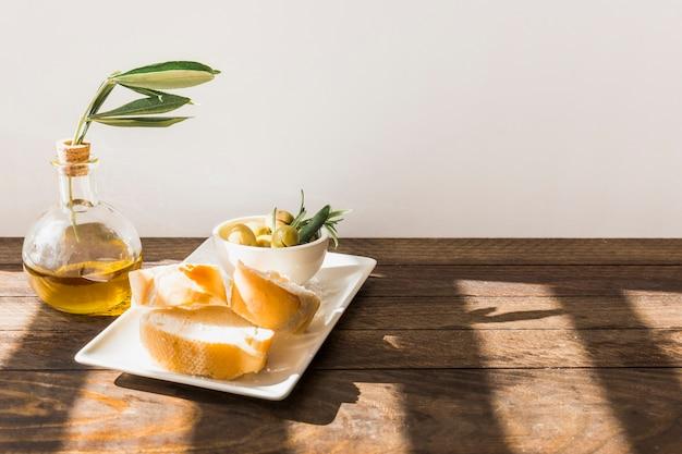 Rebanada de pan con cuenco de aceitunas en la bandeja sobre la mesa de madera contra la pared