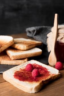 Rebanada de pan con mermelada de frambuesa y cuchara