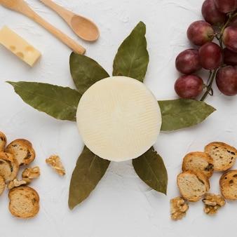Rebanada de pan nuez; uvas; hojas de laurel y cuchara de madera con queso manchego español.
