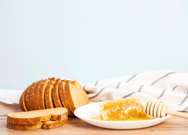 Rebanada de pan y panal para el desayuno en superficie de madera
