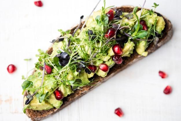 Rebanada de pan con pasta de aguacate y verduras alta vista