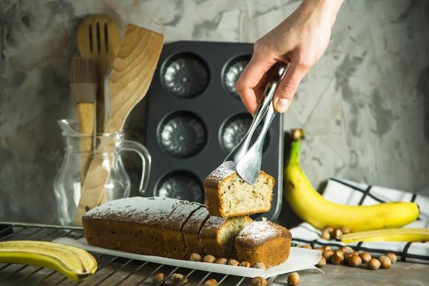 Una rebanada de pan de plátano en las pinzas en la mano femenina