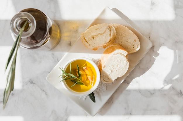 Rebanada de pan con romero y aceite de ajo en el recipiente en la bandeja