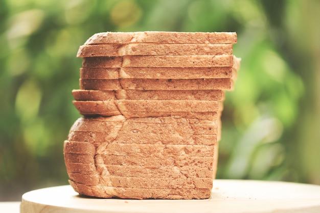 Rebanada de pan en tabla de cortar de madera y naturaleza verde