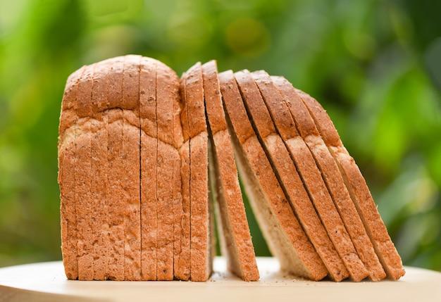 Rebanada de pan en tabla de cortar de madera