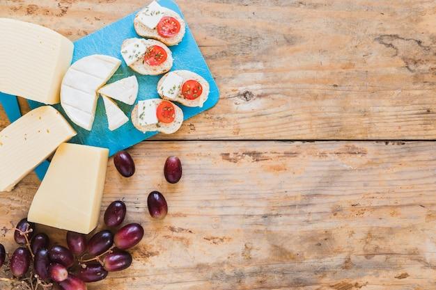 Rebanada de pan con tomate y queso con uvas en la mesa