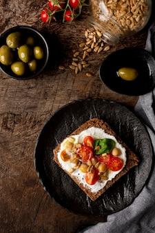 Rebanada de pan tostado delicioso con tomates cherry en la mesa de la cocina