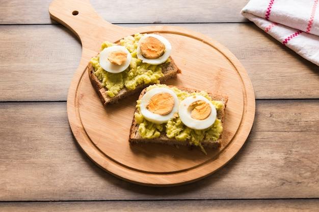 Rebanada de pan tostado con huevo cocido en tabla de cortar