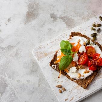 Rebanada de pan tostado con tomates cherry en mármol vista alta