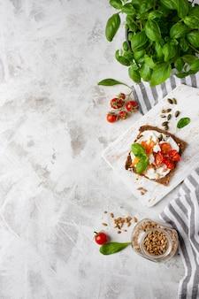 Rebanada de pan tostado con tomates cherry sobre fondo de mármol