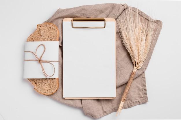 Rebanada de pan vista superior con portapapeles en blanco y toalla