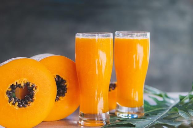 Rebanada de papaya y vasos de jugo de papaya en hoja verde