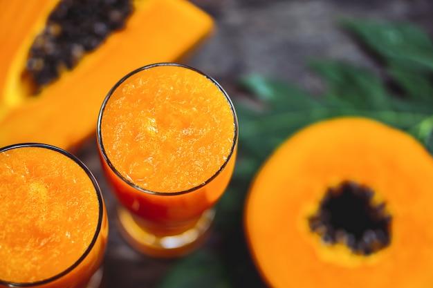 Rebanada de papaya y vasos de jugo de papaya en mesa