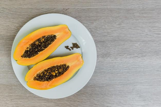 Rebanada de papayas maduras en mesa de madera con vintage y viñeta, fruta saludable