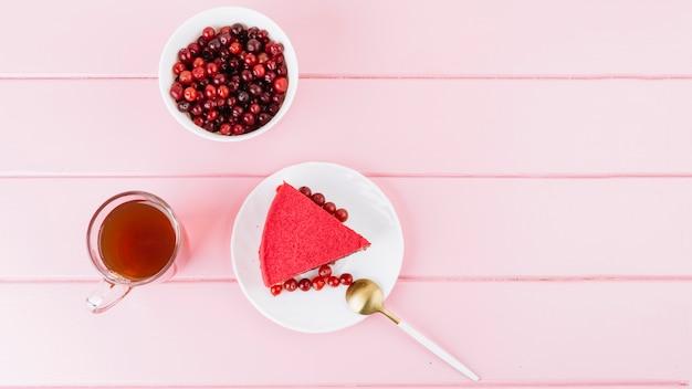 Rebanada de pastel de bayas de grosella roja; jugo y bayas en fondo de madera rosa