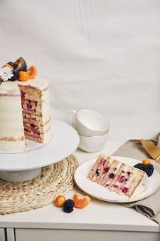 Rebanada de pastel con bayas y maracuyá en la mesa detrás de un fondo blanco.