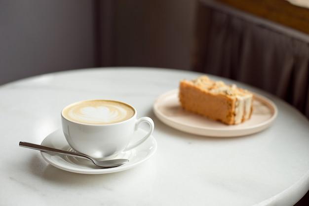 Rebanada de pastel de caramelo y taza de café caliente.