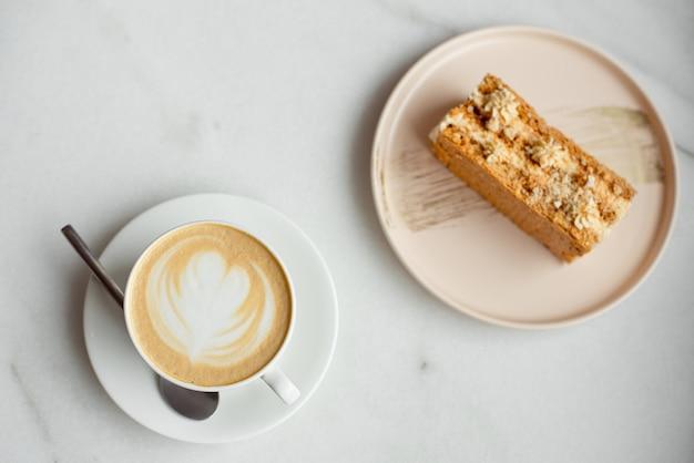 Rebanada de pastel de caramelo y un tenedor en el lado derecho. una taza de café caliente, vista superior