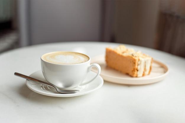 Rebanada de pastel de caramelo y un tenedor en el lado derecho. una taza de cafe caliente