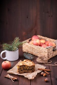 Rebanada de pastel con cesta de manzanas y castañas