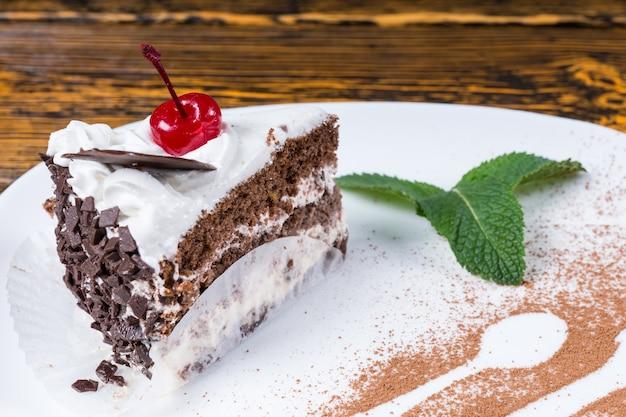 Rebanada de pastel de chocolate cremoso recién horneado servido en un plato con detalle decorativo de una cuchara y tenedor en chocolate en polvo en un restaurante gourmet