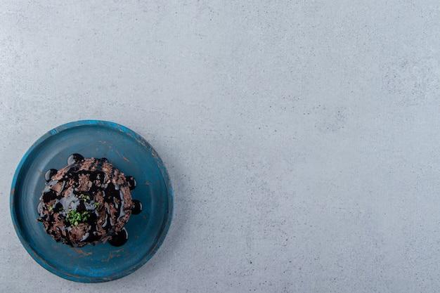 Rebanada de pastel de chocolate decorado con syrop en placa azul. foto de alta calidad