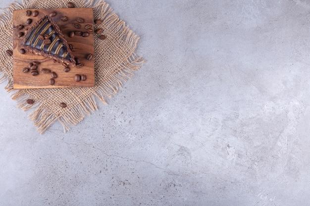 Rebanada de pastel de chocolate con granos de café colocados sobre la superficie de la tela de saco.