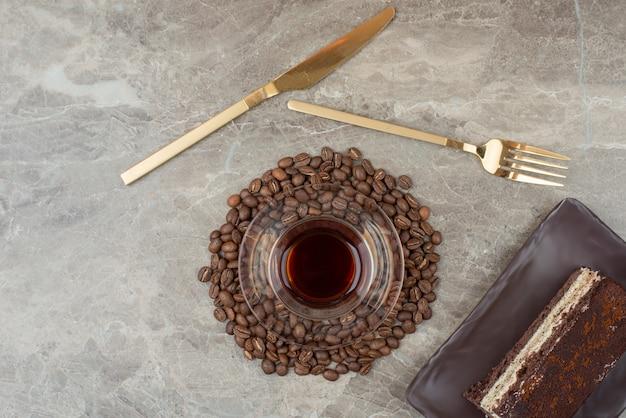 Rebanada de pastel de chocolate, granos de café y vaso de té en la mesa de mármol.