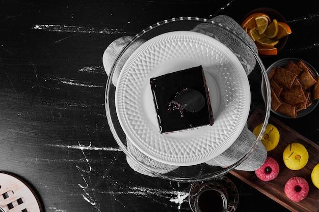Una rebanada de pastel de chocolate en un plato blanco con frutas y galletas.