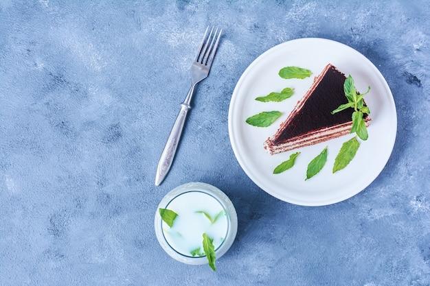 Una rebanada de pastel de chocolate en un plato blanco con leche.