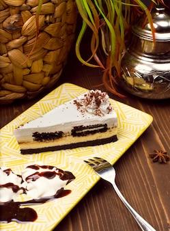 Rebanada de pastel de chocolate y vainilla en un plato contra una mesa rústica de madera marrón