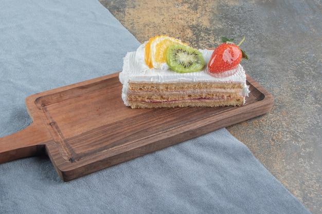 Rebanada de pastel con crema y frutas sobre una pequeña tabla de madera