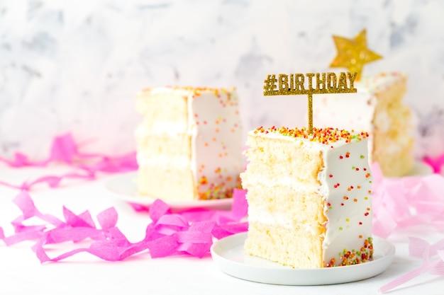 Rebanada de pastel de cumpleaños y decoración de papel rosa