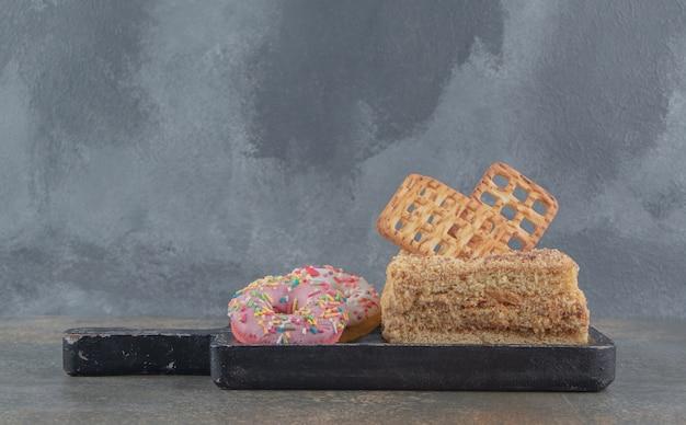 Rebanada de pastel con galletas y pequeñas donas en una bandeja negra