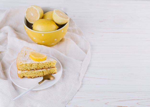 Rebanada de pastel de limón en un plato blanco con limones en rodajas en un tazón