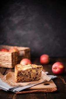 Rebanada de pastel con manzanas y cuchara de madera
