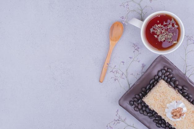 Una rebanada de pastel medovic servido con té