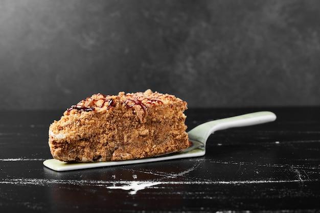 Una rebanada de pastel de miel en la espátula.
