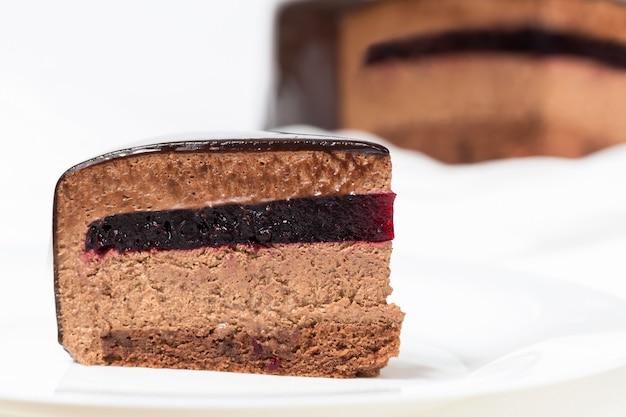 Rebanada de pastel de mousse de chocolate con gelatina de grosella y glaseado espejo