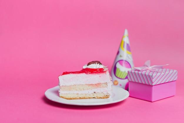 Rebanada de pastel en plato con sombrero de fiesta y caja de regalo en fondo rosa