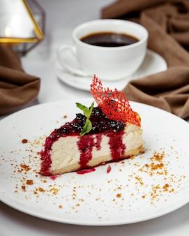 Rebanada de pastel de queso de grosella negra adornada con grosella negra y jarabe