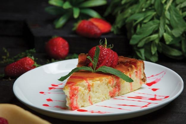 Rebanada de pastel de queso con hojas de fresa y menta