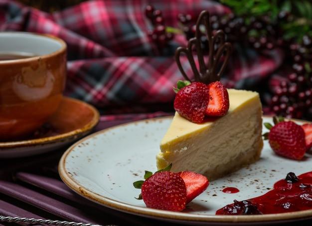 Rebanada de pastel de queso de vainilla con fresas.