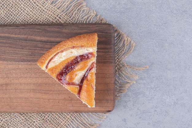 Una rebanada de pastel sobre una tabla de madera sobre una mesa de mármol.