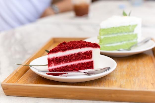 Rebanada de pastel de terciopelo rojo con cuchara de plata sobre tablero de madera