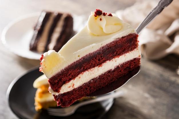 Rebanada de pastel de terciopelo rojo sobre mesa de madera