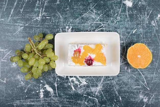 Rebanada de pastel, uvas y naranja sobre fondo azul. foto de alta calidad