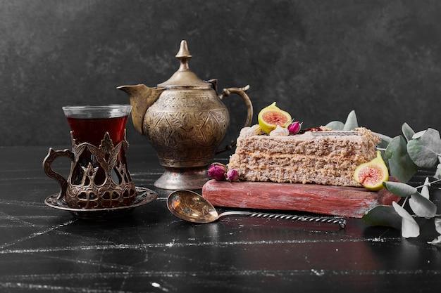 Rebanada de pastel con un vaso de té en un plato de madera.