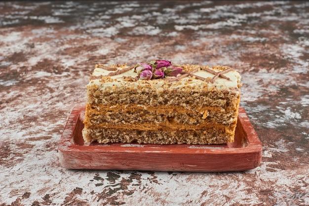Rebanada de pastel de zanahoria sobre una tabla de madera.